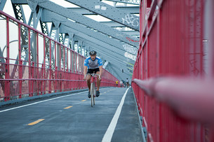 Man cycling over bridgeの写真素材 [FYI03476553]