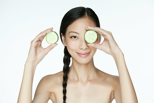 Woman holding cucumber over eyeの写真素材 [FYI03476563]