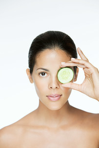 Woman holding cucumber over eyeの写真素材 [FYI03476568]
