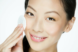 Young woman using cotton pad on faceの写真素材 [FYI03476569]
