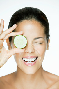 Woman holding cucumber over eyeの写真素材 [FYI03476577]