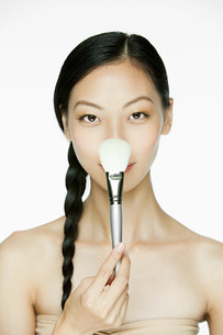 Young woman with makeup brushの写真素材 [FYI03476581]