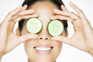 Woman holding cucumber over eyesの写真素材 [FYI03476586]
