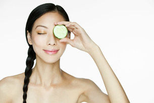 Woman holding cucumber over eyeの写真素材 [FYI03476602]