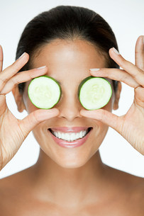 Woman holding cucumber over eyesの写真素材 [FYI03476607]