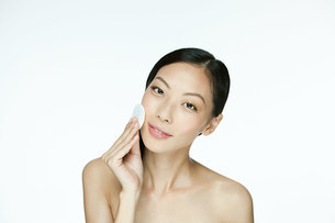 Young woman using cotton pad on faceの写真素材 [FYI03476615]