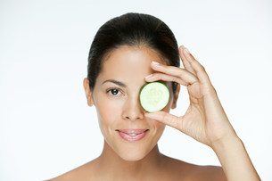 Woman holding cucumber over eyeの写真素材 [FYI03476617]