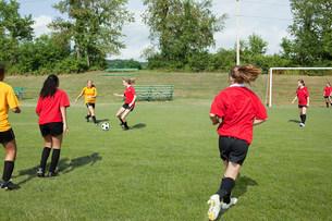 Teenage girls playing soccerの写真素材 [FYI03476645]