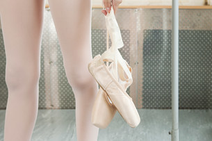 Close up on ballerina holding ballet shoesの写真素材 [FYI03476891]