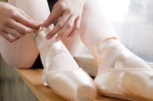 Girl tying ballet shoesの写真素材 [FYI03476901]