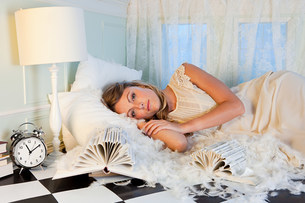 Young woman lying amongst pillow feathers in small roomの写真素材 [FYI03476985]