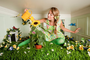 Young woman with garden in small roomの写真素材 [FYI03476988]