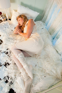 Young woman sleeping amongst pillow feathersの写真素材 [FYI03477002]