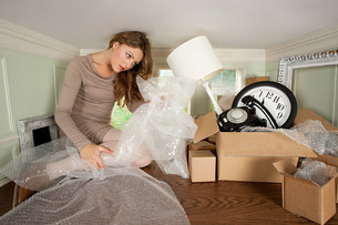 Young woman packing box of objects in small roomの写真素材 [FYI03477026]