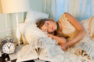 Young woman sleeping amongst pillow feathersの写真素材 [FYI03477029]
