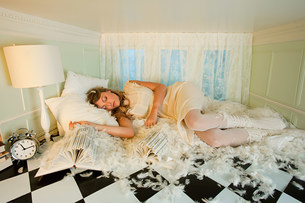 Young woman sleeping amongst pillow feathers in small roomの写真素材 [FYI03477045]