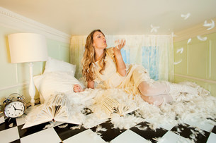 Young woman in small room,blowing pillow feathersの写真素材 [FYI03477061]