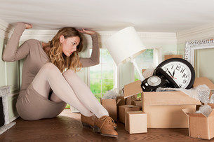 Young woman with box of objects in small roomの写真素材 [FYI03477062]