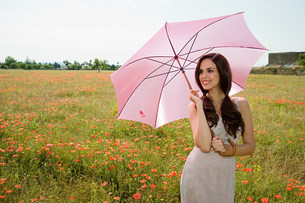 Young woman in poppy field with pink parasolの写真素材 [FYI03477077]
