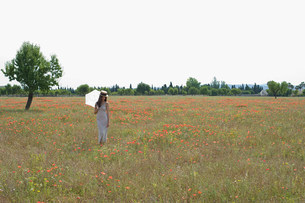Young woman standing in poppy field with white parasolの写真素材 [FYI03477078]