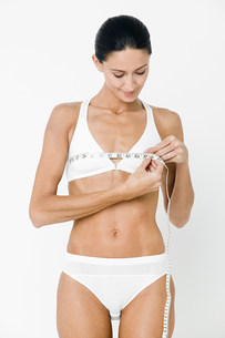 Young woman measuring breasts with tape measureの写真素材 [FYI03477197]