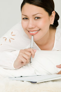 Young woman writing diaryの写真素材 [FYI03477228]