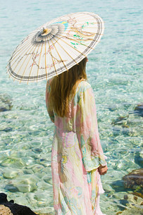 Young woman on vacation with parasolの写真素材 [FYI03477241]