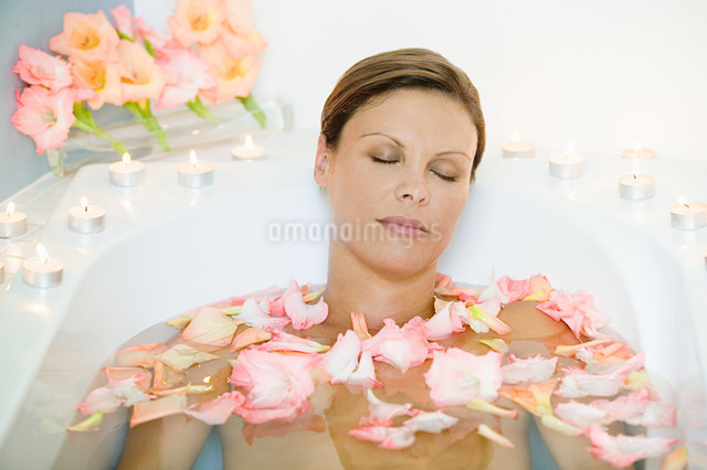 Young woman in bath with petalsの写真素材 [FYI03477257]