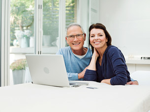 Mature couple using laptop with credit cardの写真素材 [FYI03477406]