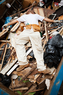 Man lying on top of pile of rubble in skipの写真素材 [FYI03477456]
