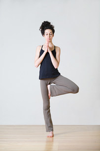 Woman in tree position during yogaの写真素材 [FYI03477776]