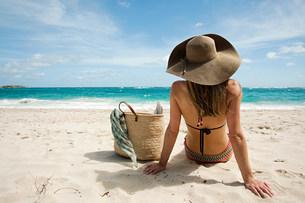 Woman sitting on sandy beach, Mustique, Grenadine Islandsの写真素材 [FYI03477962]