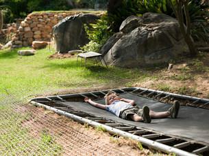Boy lying on trampolineの写真素材 [FYI03478197]
