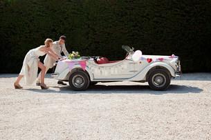 Newlyweds pushing broken down vintage carの写真素材 [FYI03478238]