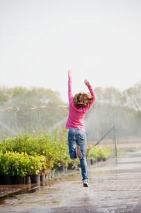Girl skipping along path in plant nurseryの写真素材 [FYI03478417]