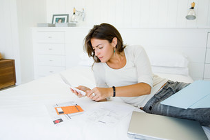 Woman on bed organising home financesの写真素材 [FYI03478486]