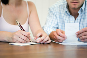 Couple planning home finances, woman writing chequeの写真素材 [FYI03478488]