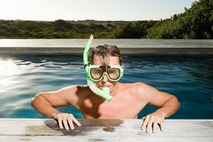 Young man wearing snorkel at poolsideの写真素材 [FYI03478528]