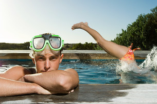 Young man wearing snorkel at poolside, woman diving inの写真素材 [FYI03478529]