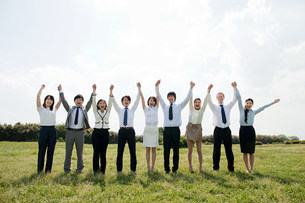 Businesspeople in a row in field, arms upの写真素材 [FYI03478568]