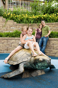 Two girls sitting on top of tortoise statue at the zooの写真素材 [FYI03478635]