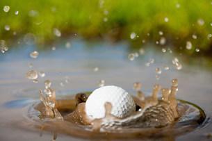 Golf ball splashing into waterの写真素材 [FYI03478687]