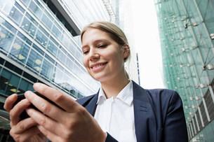 Businesswoman using smartphone amongst office buildingsの写真素材 [FYI03478739]