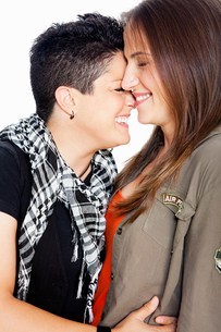 Lesbian couple smiling against white backgroundの写真素材 [FYI03478760]