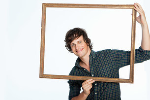 Mid adult man holding picture frame against white backgroundの写真素材 [FYI03478776]