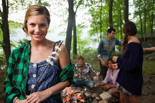 Young woman holding food cooked on campfire in forestの写真素材 [FYI03478901]