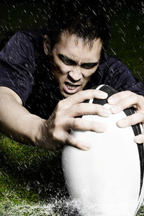 Rugby player with ball in the rainの写真素材 [FYI03479040]