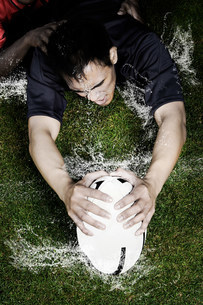 Rugby tackle on wet groundの写真素材 [FYI03479041]