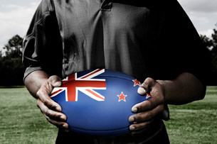 Player holding rugby ball with New Zealand flagの写真素材 [FYI03479042]