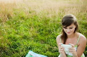 Young woman looking at a hand held device in a fieldの写真素材 [FYI03479123]